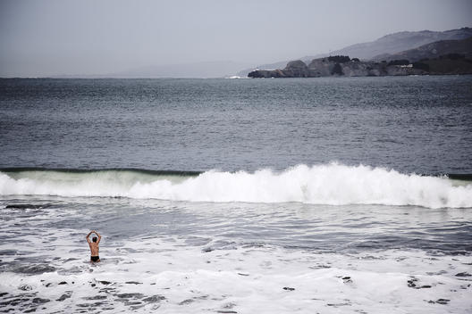 An athletic man eases into the frigid waters off the Northern California Coast