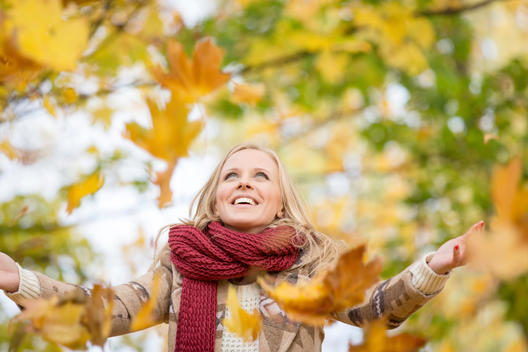 Poland, Warsaw, Blonde woman throwing autumn leaves