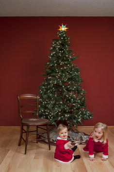 Sisters, dressed in holiday outfits, play together next to a Christmas tree.