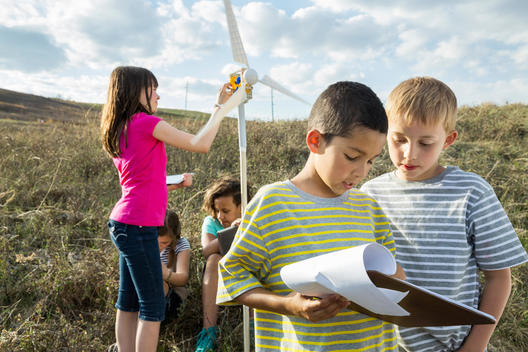 Boys discussing over document and girls with windmill during field trip