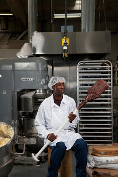 In a bakery a man holds up a paddle covered in chocolate batter