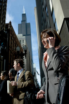 A Business Woman Talks On Her Cell Phone At A Busy Chicago Street Corner.