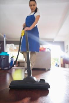 Woman vacuuming living room floor