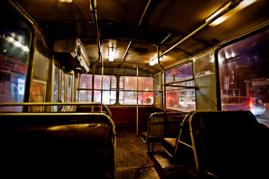 Interior of an empty bus at night.