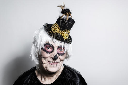Portrait of senior woman with sugar skull make-up and fancy hat