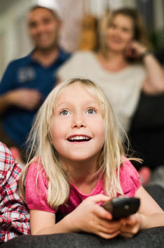 Little girl with remote control watching TV and parents sitting in background