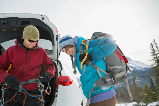 Man and woman preparing for winter hike in mountains