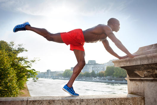 Athletic man stretching on top of bridge, Seine River in background