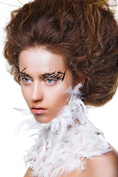 Shot of the model with volume hair and unusual makeup, like a bird. There is a plumage on her neck.