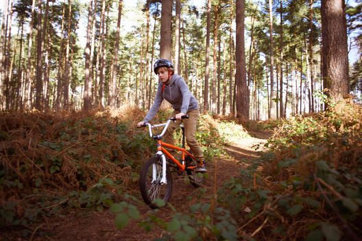Boy riding his BMX in forest