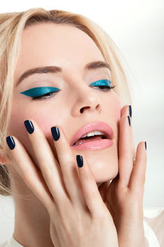 Caucasian model wearing a bright thick metallic turquoise eyeliner holding her face with her hands, her nails are painted with black textured nail polish, published in Lucire magazine