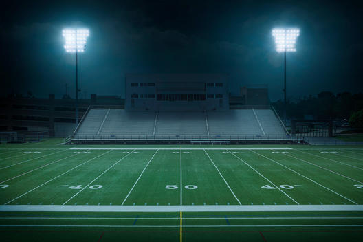 College football field with a view from the bleachers of the 50 yard line at night.