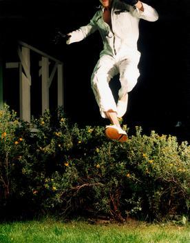 Man Jumping Over Flower Bush