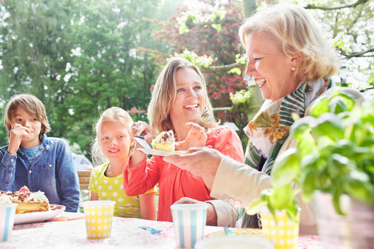 Mother serving birthday cake to family at birthday party