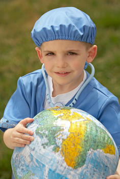 Young Boy Wearing Dress Up Doctor Suit And Holding Globe