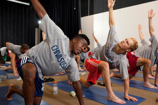 Players from the Chivas soccer team kneel on mats doing yoga poses together