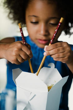 Little girl eating takeout food with chopsticks