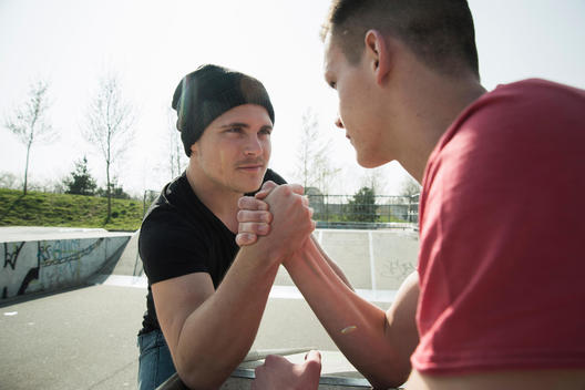 Young men arm-wrestling in skatepark