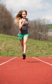 Austria, Teenage girl running on track, portrait
