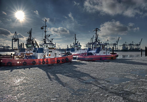 Germany, Hamburg, View of tugs moored at harbour on frozen water