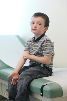Boy Sitting On Doctors Check Up Table