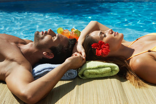 Couple relaxing at edge of swimming pool