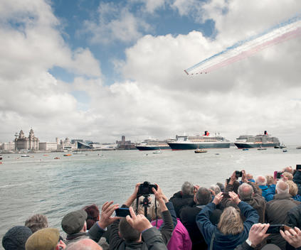 Crowds of spectators photograph the \'Red Arrows\' air display team as they perform a fly past over the \'Three Queens\' of the Cunard Fleet in the River Mersey, Liverpool. The Queen Mary 2, The Queen Elizabeth 2 and the Queen Victoria.