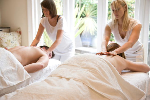Two masseuses giving two people a massage