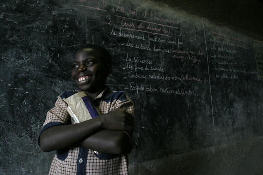 Niyoyit Twizerimana, Age 13. Young student with his text book stands by a blackboard with writing from a geography lesson at a school in Rwanda, East Africa. African children studying. African school. Attentive students. 10th anniversary of the Rwandan Ge