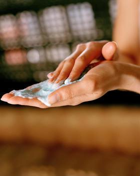 woman rubbing cream into hands