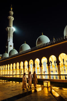 Three Arab men walk at night along the lit up exterior of Sheikh Zayed Grand Mosque in Abu Dhabi.