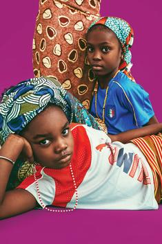 kids fashion shoot in studio with colorful background mixing european football jerseys with traditional african clothes and textiles