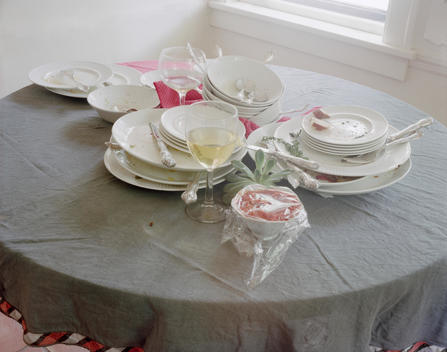 Grey Blue Tablecloth With Piles Of White Dishes Littered With Food, Cutler, Glasses, Pink And Red Napkins