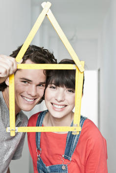 Germany, Cologne, Young couple holding house model pocket ruler in front of them