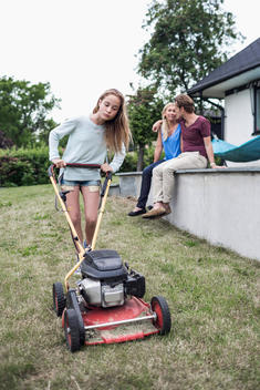 Girl mowing lawn with parents sitting in background at yard