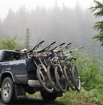 Row of mountain bikes loaded on the back of a pick-up truck in a forest, Glacier, Washington, USA.