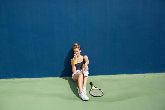 woman sits at the edge of a tennis court and drinks a beverage.