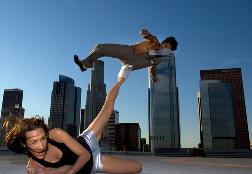 Couple fighting martial arts on building rooftop