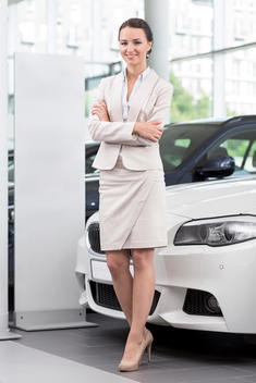 At the car dealer, Smiling Saleswoman at new car