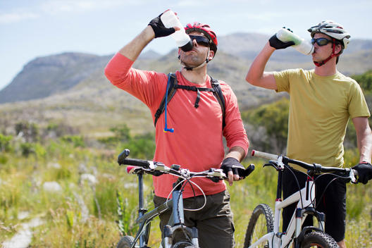 mountain bikers driving water in rural landscape
