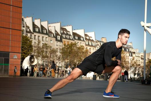 Athletic man stretching in urban setting