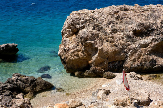 High Angle View Of Rocky Shore, Turquise Water, Sea And Closed Sun Umbrella.