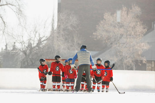 Coach instructing ice hockey team on rink