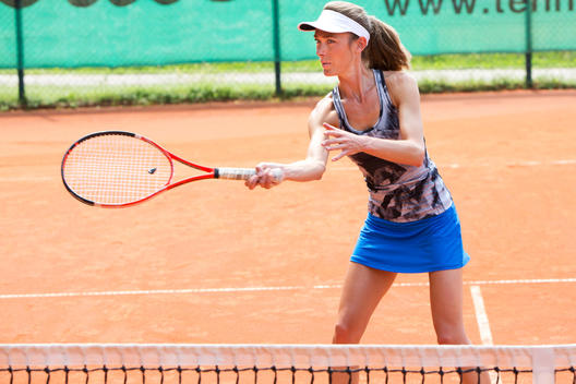 Female tennis player playing on tennis court