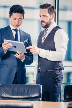 caucasian businessman with beard and Asian businessman standing in office and talking while holding a tablet computer