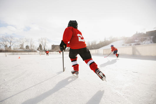 Rear view of boy playing ice hockey on rink