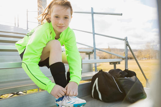Portrait of soccer player tying shoelace on bleachers
