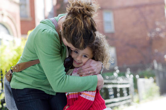 A Mother Hugs Her Daughter In A Residential Chicago Neighborhood On A Sunny Day.