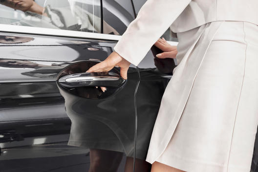 At the car dealer, Woman opening car door