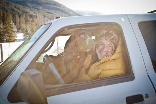 Portrait of a man and his dog in a truck.
